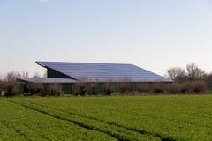 Große Scheune mit Sonnenkollektoren und Grünfeld Stockbild