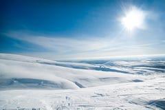 Große schneebedeckte Felder unter der Sonne Lizenzfreie Stockfotografie