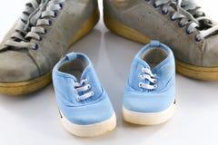 Große Schuhe des Vaters und der kleinen Babyschuhe Stockfotos