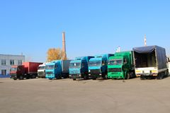 Große Schwergut-LKWs mit Fahrerhäusern und Anhängern stehen in Folge zur Lieferung der Fracht an der industriellen Raffinerie ber stockbild