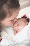 Große Schwester, die ihren neugeborenen Bruder küsst Stockbild