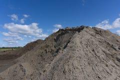 Große Stapel des Bausandes und -kieses benutzt für Asphaltproduktion und -gebäude Kalksteinsteinbruch, Bergbaufelsen und Steine stockfotografie