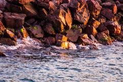 Große steile Felsen im Sonnenuntergang mit gewelltem Meer Stockfoto