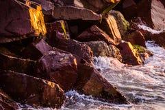 Große steile Felsen im Sonnenuntergang mit gewelltem Meer Lizenzfreies Stockbild