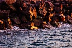 Große steile Felsen im Sonnenuntergang mit gewelltem Meer Stockbilder