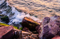 Große steile Felsen im Sonnenuntergang mit gewelltem Meer Lizenzfreie Stockbilder