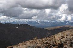 Große Steine auf dem Hintergrund des hoher Gebirgsschnees ragt Strecken empor Stockfotos