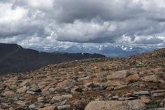 Große Steine auf dem Hintergrund des hoher Gebirgsschnees ragt Strecken unter bewölkten Trübsinnbewölkten himmel empor Stockfotografie