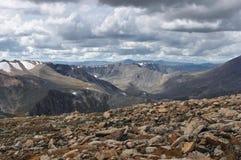 Große Steine auf dem Hintergrund von Schneespitzenstrecken des Tales und des hohen Berges Stockbilder