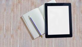 Große Tablette des leeren Bildschirms und leeres Anmerkungsbuch auf Holztisch Lizenzfreie Stockfotos