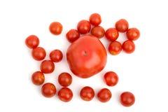 Große Tomate auf dem Hintergrund der kleinen Kirsche Stockfoto