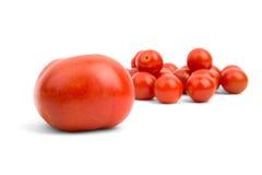 Große Tomate auf dem Hintergrund der kleinen Kirsche Stockbilder