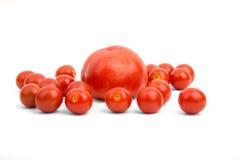 Große Tomate umgeben durch kleine Kirsche Lizenzfreie Stockfotografie
