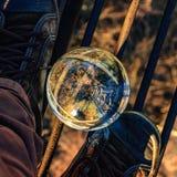 Große transparente Glaskugel unter den Füßen in der industriellen Umwelt, auf dem Hoch Stockbilder