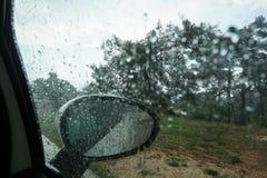 Große Tropfen des Regens fließen hinunter die Windschutzscheibe des Autos, die Ansicht vom Auto stockbild