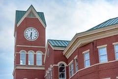 Große Uhr auf Regierungs-Gebäude des roten Backsteins Stockfoto