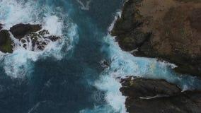 Große von der Luftwelle, die auf Felsenküste zusammenstößt stock footage