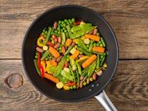 Große Wanne briet mit buntem Gemüse - Pfeffer, Erbsen, grüne Bohnen, Babymais, Karotten, Bohnen Das bunte vegetarische Mittagesse Lizenzfreie Stockfotos