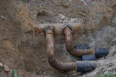 Große Wasserleitungen im Boden während der KlempnerarbeitBaustelle Lizenzfreies Stockbild