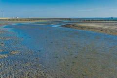 Große Wasserpfütze auf dem Strand, der zu den Ozean führt Stockfotografie