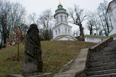 Große weiße alte christliche Kirche mit Kreuzen, grünem Dach und hölzernem Idol nahe Treppe Stockfotos