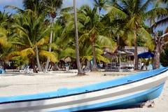 Große weiße Bootsnahaufnahme auf einem sandigen Strand mit grünen Palmen, sunbeds für die Entspannung und einem Gazebo an einem w stockbild