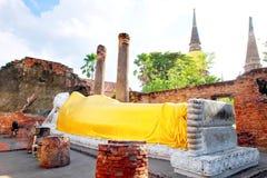 Große weiße Buddha-Statue, die einen gelben Mantel und eine Pagode mit Sonnenlicht bei Wat Yai Chaimongkol, Si Ayutthaya, Thailan stockfotografie