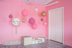 Große Weihnachtsbälle auf einem rosa Hintergrund im Kinderraum Stockfotografie