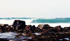 Große Welle auf dem Hintergrund von Steinen Stockfotos