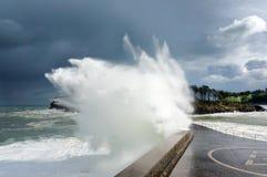 Große Welle, die auf Wellenbrecher bricht Stockfotos