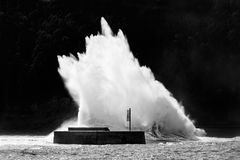 Große Welle, die auf Wellenbrecher bricht Stockbilder
