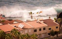 Große Welle vor einigen Häusern an der Küste; Lizenzfreies Stockbild