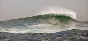 Große Wellen am bewölkten Tag. Stockfoto