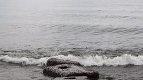 Große Wellen brechen auf einem konkreten Steinpier in einem Sturm auf dem Baikalsee in einem großen Meer stock footage
