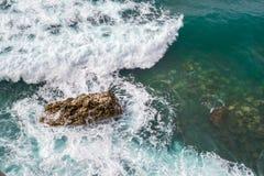 Große Wellen, die auf dem Ufer brechen Wellen und weißer Schaum Küstensteine Ansicht von oben Der Marinehintergrund ist grün Stockbilder