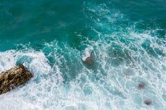 Große Wellen, die auf dem Ufer brechen Wellen und weißer Schaum Küstensteine Ansicht von oben Der Marinehintergrund ist grün Lizenzfreie Stockfotografie
