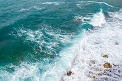Große Wellen, die auf dem Ufer brechen Wellen und weißer Schaum Küstensteine Ansicht von oben Der Marinehintergrund ist grün Stockfoto