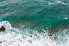 Große Wellen, die auf dem Ufer brechen Wellen und weißer Schaum Küstensteine Ansicht von oben Der Marinehintergrund ist grün Stockfotografie