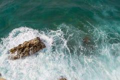 Große Wellen, die auf dem Ufer brechen Wellen und weißer Schaum Küstensteine Ansicht von oben Der Marinehintergrund ist grün Lizenzfreie Stockbilder