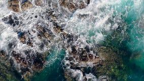 Große Wellen, die gegen Felsen auf einem Strand schlagen stock footage