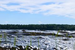 Große windige Wellen, die über Felsen spritzen Wellenspritzen im See gegen Strand Wellen, die auf einem steinigen Strand, einen S Stockbild
