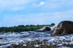 Große windige Wellen, die über Felsen spritzen Wellenspritzen im See gegen Strand Wellen, die auf einem steinigen Strand, einen S Stockfoto