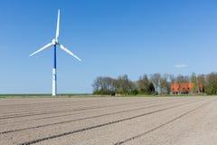 Große Windkraftanlage im Ackerland mit Bauernhaus Stockbild