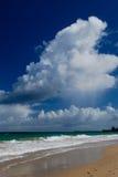 Große Wolken, die auf einen Strand überschreiten Stockbild