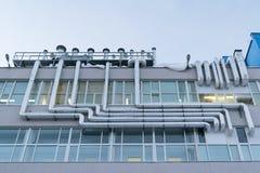 Große Zahl der Metallaluminiumrohrleitung befestigt an der Fassade des Gebäudes Stockbild