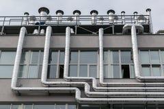Große Zahl der Metallaluminiumrohrleitung befestigt an der Fassade des Gebäudes Stockbilder