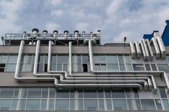 Große Zahl der Metallaluminiumrohrleitung befestigt an der Fassade des Gebäudes Stockfotografie