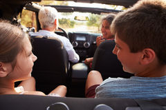 Großeltern, die Enkelkinder auf Reise im offenen Auto nehmen stockfotos