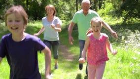 Großeltern, die Enkelkinder entlang Waldweg jagen stock video