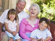 Großeltern, die mit Enkelkindern lachen Stockbild